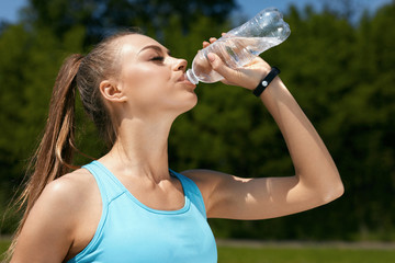 Woman Drinking Water After Running.