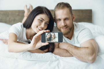 Keep smiling. Delighted couple lying on the bed and keeping smiles on faces while posing on camera