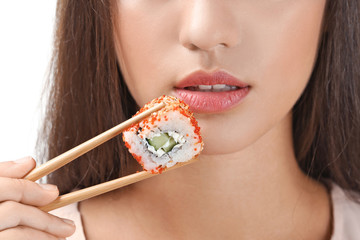 Beautiful young woman with sushi roll on white background, closeup