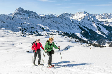 Senior couple is snowshoe hiking in alpine winter mountains. Bavaria, Germany.