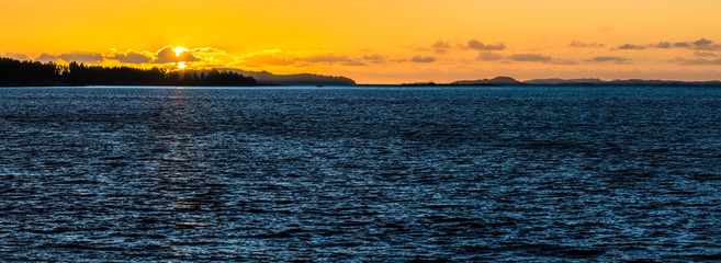 Orange sunset with deep blue water in Scandinavia. Midnight sun with reflections.