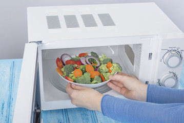 A new white microwave oven, on a blue wooden surface for heating food