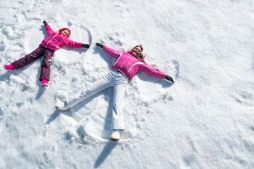 Daughter and mother laying on snow