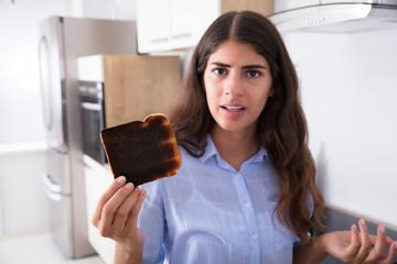 Sad Woman Looking At Burnt Toast