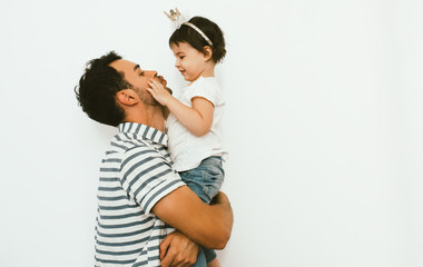 Funny dad and pretty daughter play and cuddle together against white background. Happy sincere relationship of parent and child. Family moments of father and toddler girl's birthday. Parenthood care.