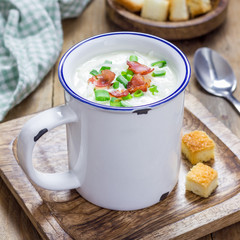 Creamy potato soup garnished with bacon and green onion, square