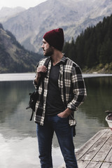Austria, Tyrol, Alps, man standing on jetty at mountain lake