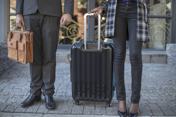Businessman and businesswoman standing with luggage