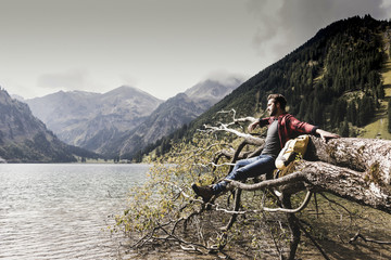 Austria, Tyrol, Alps, hiker relaxing on tree trunk at mountain lake