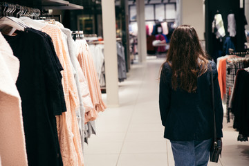 Woman looking at price tag of clothes in store
