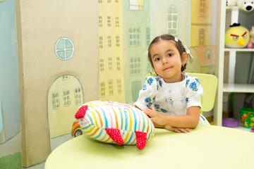 Adorable asian, Kazakh child girl in nursery room. Kid in kindergarten in Montessori preschool class.