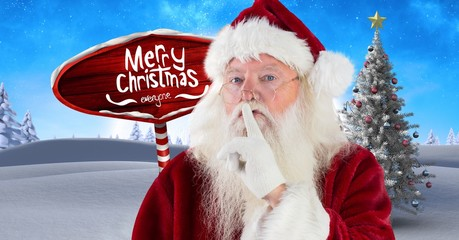 Merry Christmas text and Santa hushing quietness with Wooden