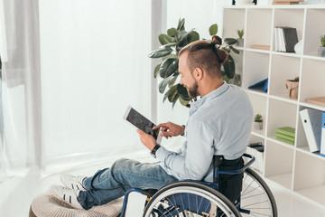 man on wheelchair using tablet