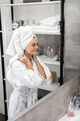 Smiling woman standing in bathroom