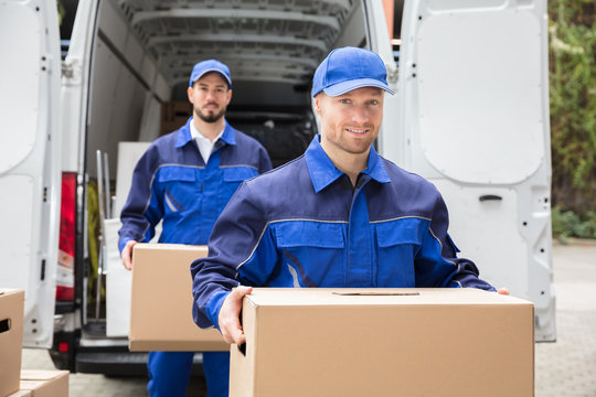 Close-up Of Two Delivery Men Carrying Cardboard Box