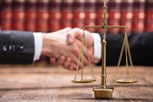 Close-up Of Justice Scale On Wooden Desk