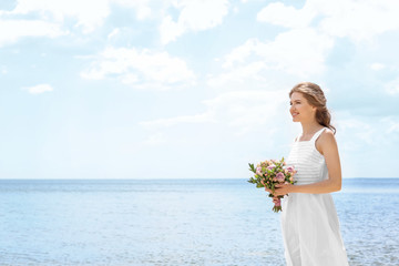 Young bride in white gown holding bouquet on seashore