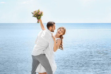 Happy newlywed couple on seashore
