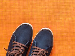 Blue sneakers on orange background