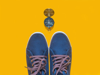 Blue sneakers and a compass on a yellow background