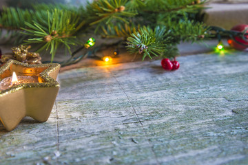 christmas holiday lights/burning candle and fir branch on rustic background with copy space
