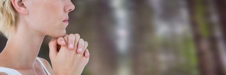 Woman in forest  clasping hands together