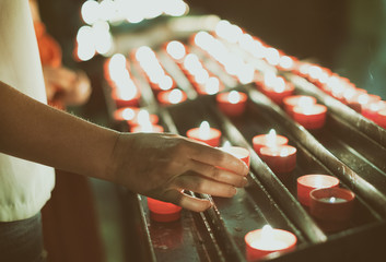 Woman puts a candle on altar in church.