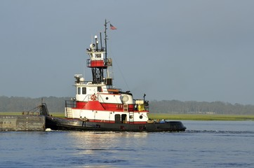 Tug boat pushing a barge on the river