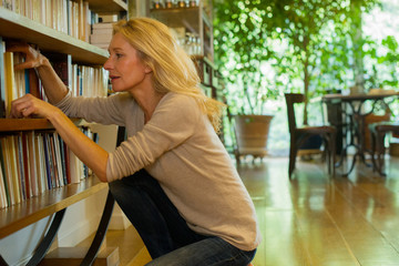 Mature woman looking at books on shelf at home