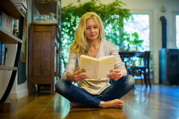 Mature woman sitting on floor at home, reading book