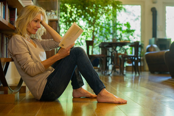 Mature woman sitting on floor reading book at home