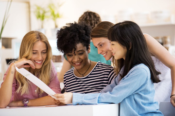 Group of friends looking at menu together in cafe