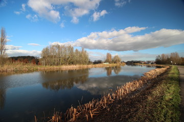 Blue sky and big clouds are reflecting in river Rotte with dike and cycle road in Oud Verlaat, Netherlands