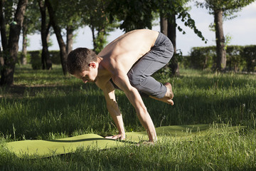 young strong man is engaged in yoga and gymnastics in the park, morning exercises, stand on his hands,  pose of a crane