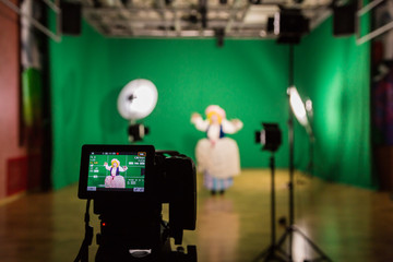 Shooting the movie on a green screen. The chroma key. Studio videography. Actress in theatrical costume. The camera and lighting equipment.