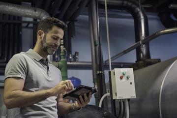 Man using digital tablet in industrial setting