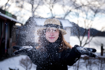 Asian beautiful woman is enjoy playing with snow.