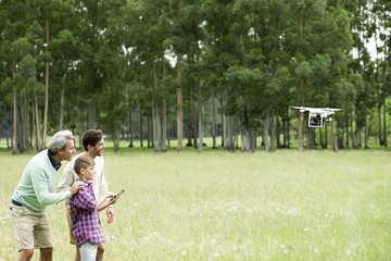 Boy flying remote control drone in open field while father and grandfather watch