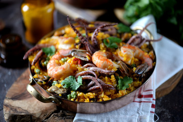Seafood squid, shrimp, mussels with rice, green peas, hot pepper, saffron, ginger and cilantro.