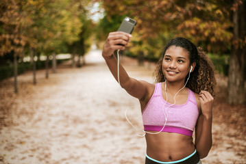 Portrait of young and attractive sports girl taking a selfie on her phone and listening music in the park.