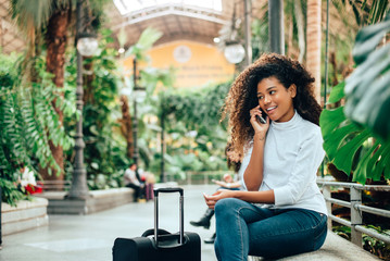 Young woman traveler with her luggage talking on phone.