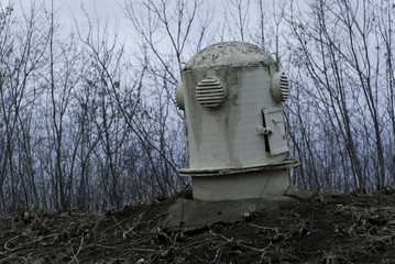 The sagging head of the ventilation shaft of an old abandoned bomb shelter in a gloomy landscape