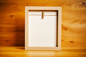 Old empty frame on a shelf on a wooden background