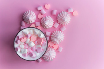 Top view hot beverage with whipped cream,marshmallows and heart shaped chocolate candies on pink pastel  background