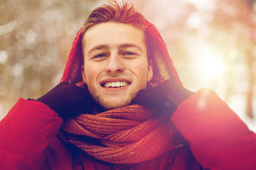 happy man in winter jacket and scarf outdoors
