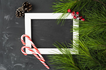 Wooden frame with christmas attributes - lollipops, fir tree, pines