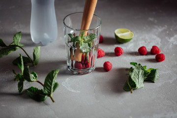 Low key shot of fresh mint, berries and cocktail equipment