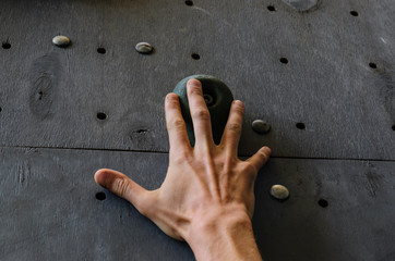 Hand of the young man on a hook of the artificial climbing wall