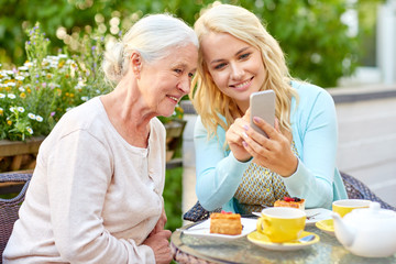 daughter and senior mother with smartphone at cafe