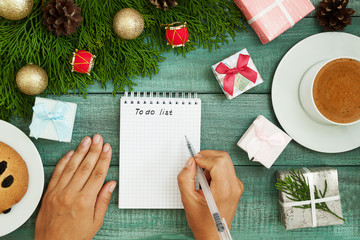 Christmas wish list writing. Woman creating present list for winter holidays. Top view, preparing for xmas and new year concept
